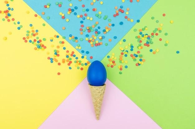 팝 컬러. 밝은 설탕 뿌리와 축제 색된 배경 종이, 웨이퍼 콘 끝 부활절 달걀에 흩어져.