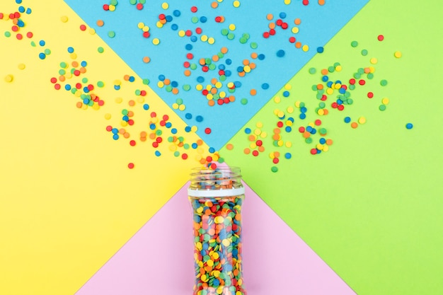 팝 컬러. 종이에 흩어져있는 밝은 설탕 뿌리와 축제 여러 가지 빛깔의 배경.