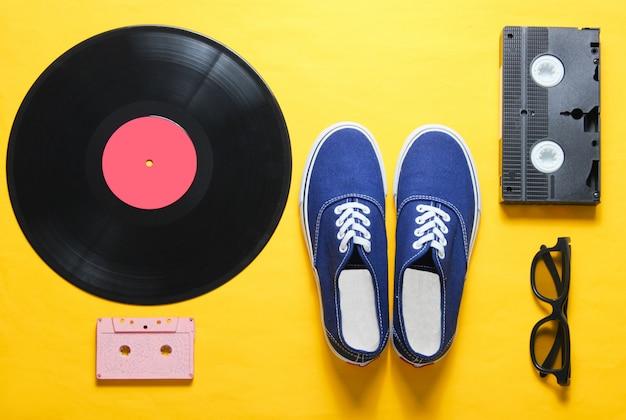 ポップカルチャー。流行に敏感なスニーカー、ビニールプレート、オーディオおよびビデオカセット、黄色の背景に3 dメガネ。