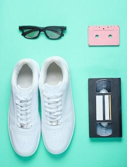 ポップカルチャー、レトロなスタイル。ホワイトヒップスタースニーカー、オーディオおよびビデオカセット、ミント色の紙の3dメガネ