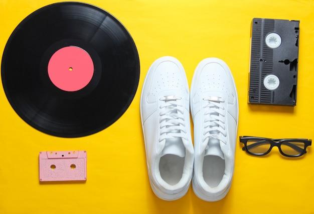 ポップカルチャー。白いヒップスタースニーカー、ビニールプレート、オーディオおよびビデオカセット、黄色の背景に3 dメガネ。
