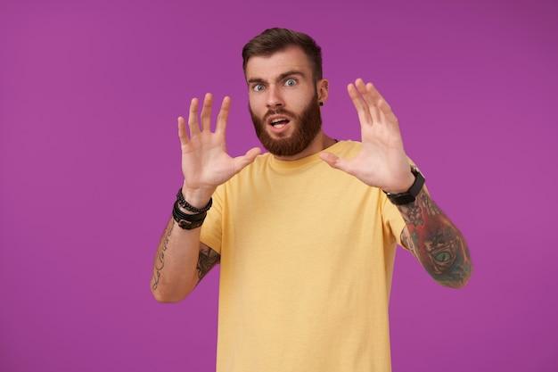 Maschio non rasato tatuato dagli occhi pop con taglio di capelli corto che guarda spaventato e alza le mani per proteggersi, in piedi sul viola in maglietta gialla