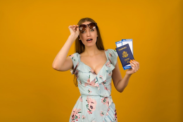 Pop-eyed young woman in blue dress with flowers and sunglasses is holding airline tickets with a passport on a yellow background. rejoices in the resumption of tourism after the coronovirus pandemic.