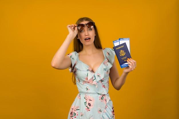 Взглянувшая молодая женщина в синем платье с цветами и солнцезащитными очками держит билеты на самолет с паспортом на желтом фоне. радуется возобновлению туризма после пандемии коронавируса.