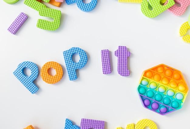Поп это надпись. самая модная сенсорная игрушка. популярная модная силиконовая красочная антистрессовая шестиугольная игрушка.