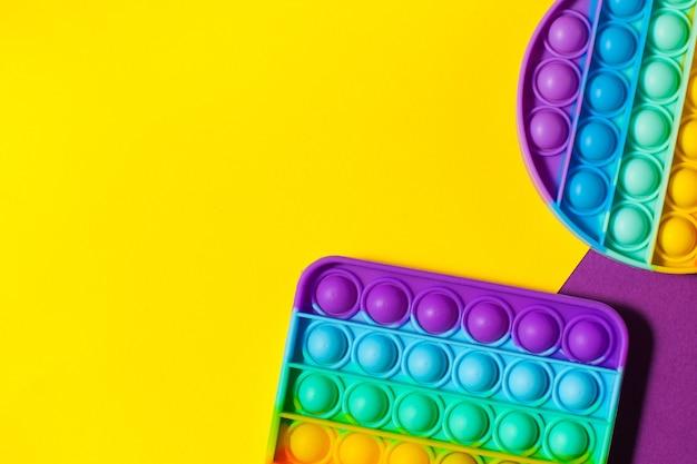 Pop it toy силиконовая на желтом фоне игрушка-антистресс тренд в детских игрушках copy space