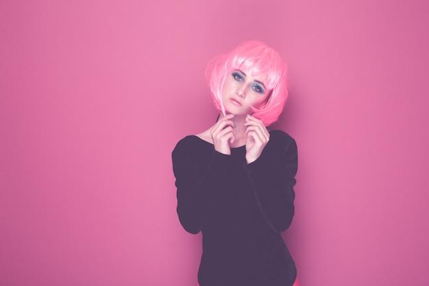 孤立したカメラでポーズをとるピンクのかつらと黒い服を着たポップスタイルの女性。