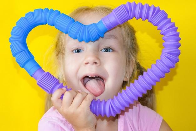 ポップチューブ。子供の手のポップチューブからの抗ストレス感覚プラスチックおもちゃ。おもちゃのそわそわポップチューブで遊んでいる陽気な女の子。 2021年のトレンド。黄色の背景