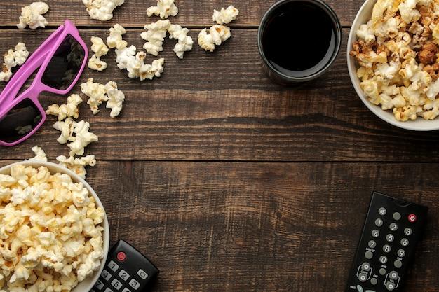 Попкорн, очки 3d и пульт от телевизора на коричневом деревянном фоне. концепция просмотра фильмов дома. вид сверху