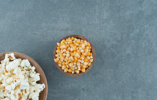 Зерна попкорна и кукурузы в мисках на мраморном фоне. фото высокого качества
