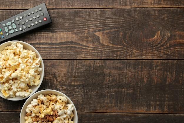 茶色の木製テーブルの上のポップコーンとテレビのリモコン、自宅で映画を見るというコンセプト、上面図
