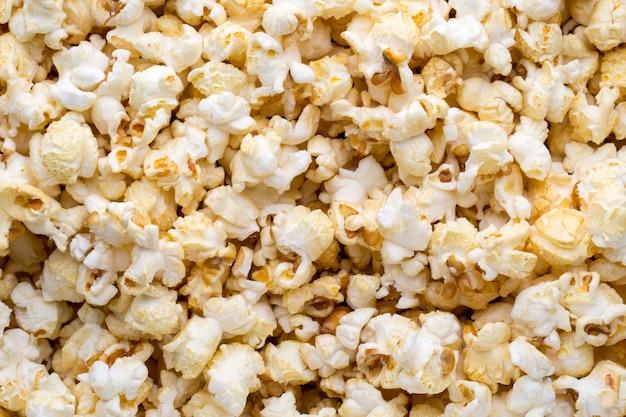 Фон попкорна. карамель сладкая кукуруза. закуска в кино.