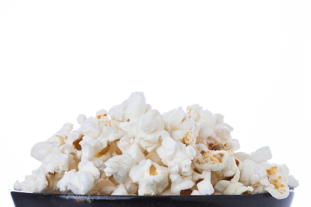 Popcorn in a black bowl isolated on white background