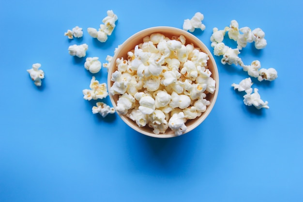 Popcorn in a bowl on blue table.
