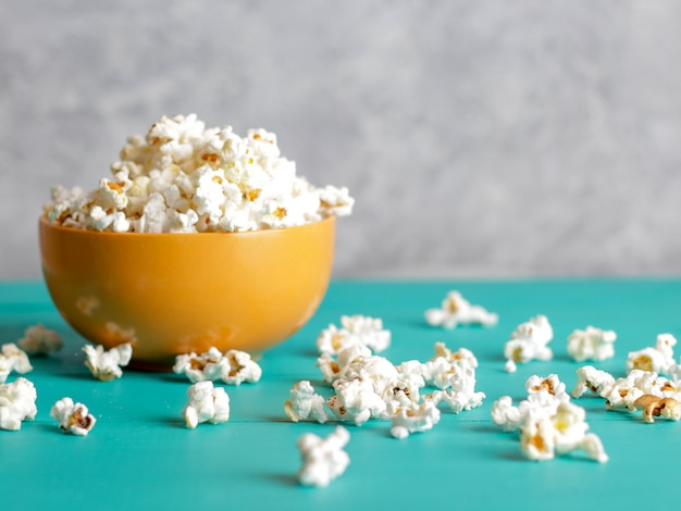 Popcorn in bowl on blue wood