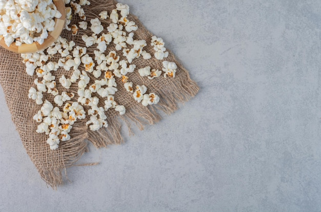Popcorn in a bowl and scattered on a piece of cloth on marble surface