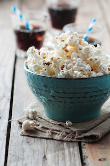 Popcorn in bowl and soda on wooden table