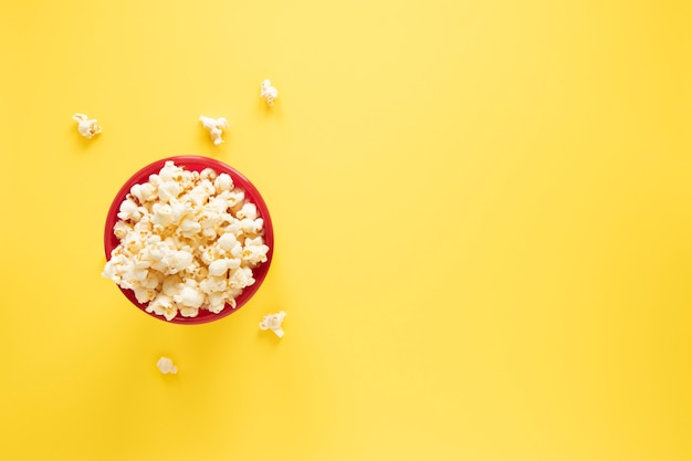Popcorn bowl on yellow background with copy space