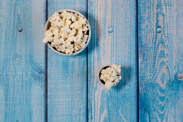 青い木製の背景にポップコーンボウル。父と息子の計画。家で映画を見る