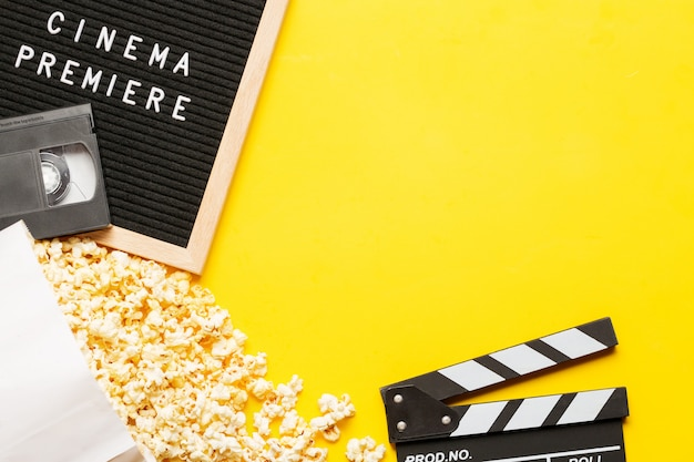 Popcorn in a box, movie clapper, vhs video cassette tape and letter board with words cinema premiere on yellow background.