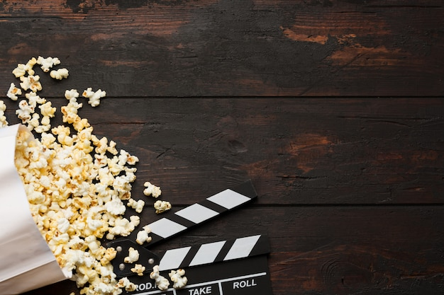 Popcorn in a box and movie clapper on wooden background top view.