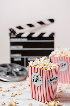 Popcorn boxes with film reel and clapperboard on wooden desk