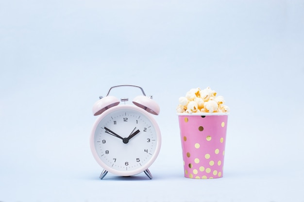 Popcorn in a bright glass and alarm clock on blue