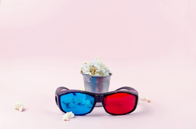 Popcorn in a bucket and 3d glasses on pink