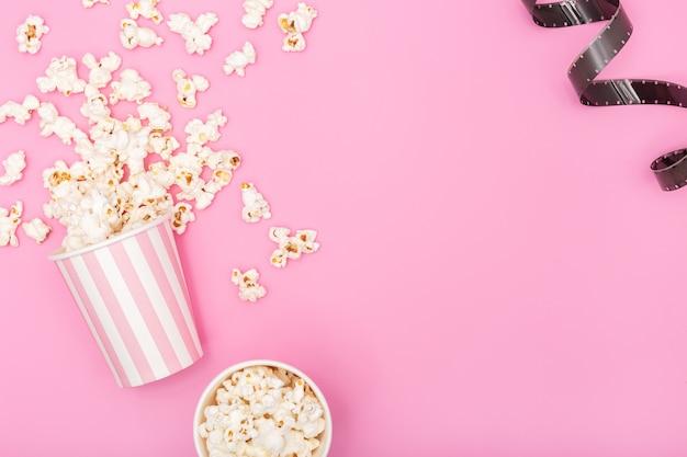 ピンクの背景のポップコーンバケツとフィルムストリップ。映画やテレビの背景。トップビューコピースペース