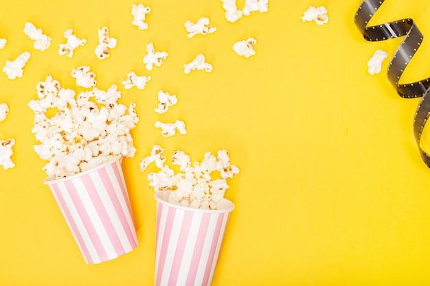 黄色の背景にポップコーンバケツとフィルムストリップ。映画やテレビの背景。トップビューコピースペース