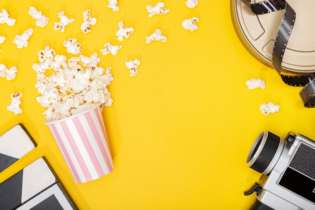 ポップコーンバケツ、フィルムカメラ、缶、黄色の背景にクラッパー。映画やテレビの背景。トップビューコピースペース