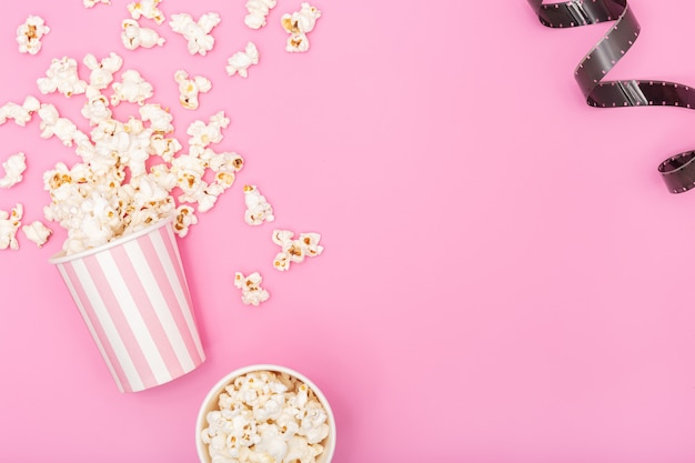 Popcorn bucket and film strip on pink background. movie or tv background. top view copy space