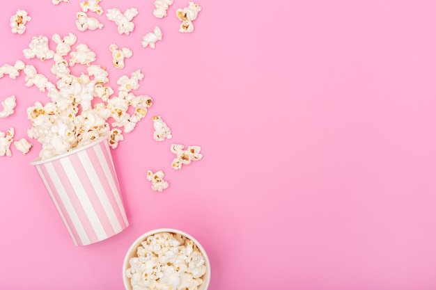 ピンクの背景のポップコーンバケツ。映画やテレビの背景。トップビューコピースペース