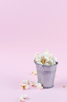 Popcorn in a bucket on pink