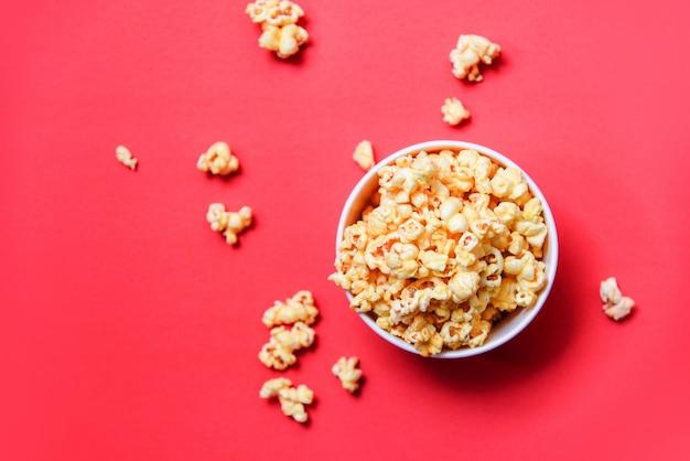 Popcorn in bucket on red  / sweet butter popcorn salt