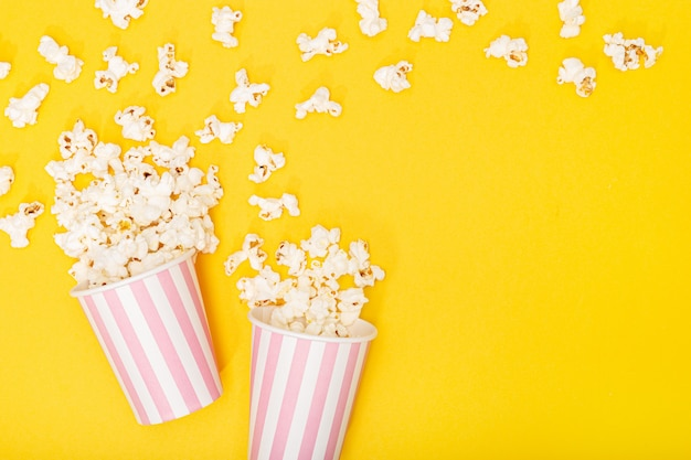 Popcorn bucket on yellow background. movie or tv background. top view copy space