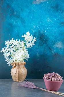 Popcorn candy in a bowl next to purple wheat stalks and white lilies in a wrapped vase on blue