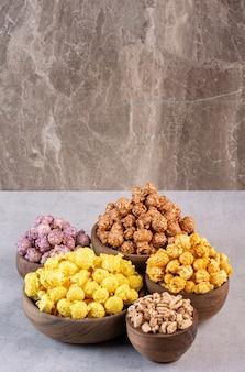 Caramelle e fiocchi di popcorn ammucchiati in ciotole su marmo.