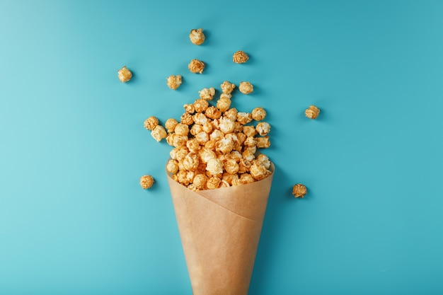 Popcorn in caramel glaze in a paper envelope on a blue background. delicious praise for watching movie movies, serial, cartoon. free space, top view. minimalistic concept.
