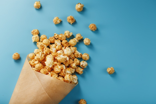 Popcorn in caramel glaze in a paper envelope on a blue background.