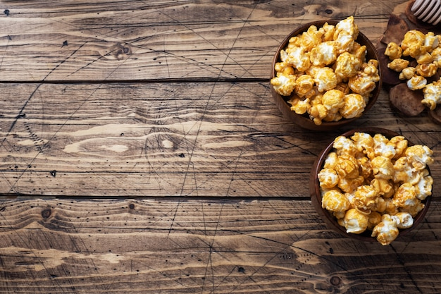 Popcorn in caramel glaze in wooden plates on a rustic table.