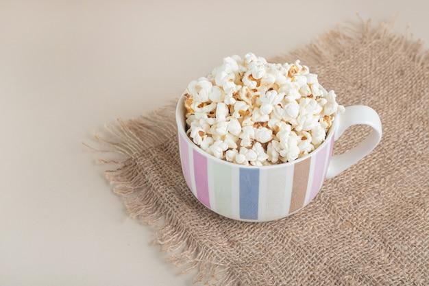 Popcorn in una tazza di ceramica su un pezzo di tela.
