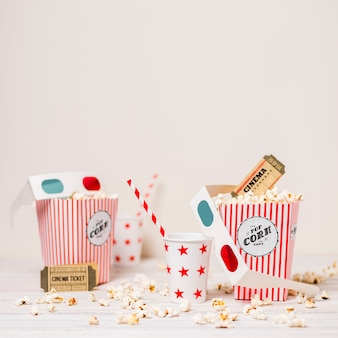 Popcorn; cinema ticket; disposable glass with drinking straw and popcorn box on table against white background