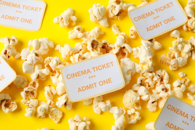 Popcorn and cinema tickets on yellow background