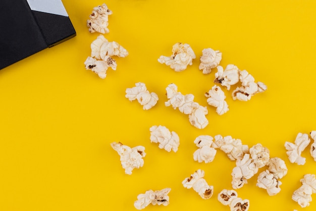 Popcorn and clapperboard on colorful background. top view