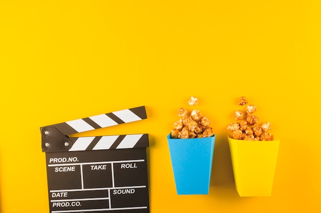 Popcorn and clapperboard on yellow table. top view