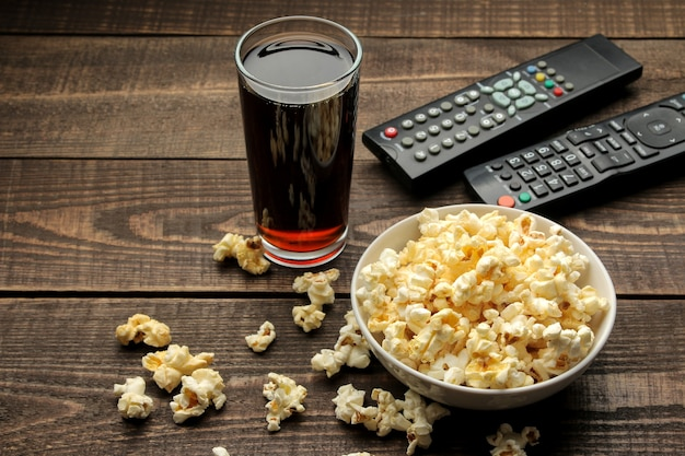 Popcorn, coca cola and tv remote on a brown wooden table, concept of watching movies at home.