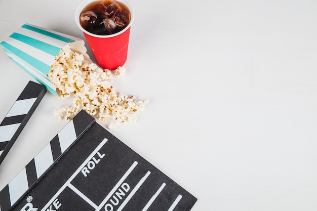 Popcorn and cola near clapperboard