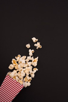 Popcorn composition on black background with copy space