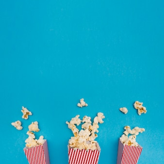 Popcorn composition on blue background with copy space